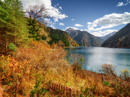 long lake: Beautiful view of the Long Lake among colorful fall woods and mountains in Jiuzhaigou nature reserve (Jiuzhai Valley National Park), China. Amazing snowy peaks and blue sky are visible in background.