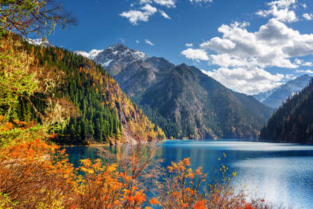 Fantastic view of the Long Lake among mountains and colorful fall woods in Jiuzhaigou nature reserve (Jiuzhai Valley National Park), China. Beautiful snowy peaks and blue sky are visible in background