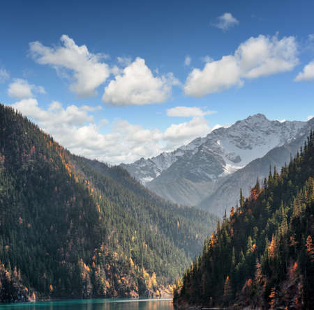 long lake: Fantastic view of snow-capped mountains on blue sky background. Snowy peaks, wooded mountains and the Long Lake in Jiuzhaigou nature reserve (Jiuzhai Valley National Park), China. Beautiful landscape. Stock Photo