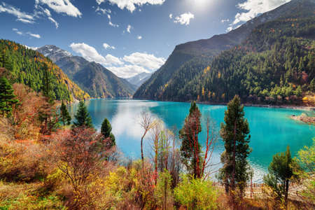 Amazing view of the Long Lake with azure water among fall woods and mountains in Jiuzhaigou nature reserve (Jiuzhai Valley National Park), China. Beautiful snowy peaks are visible in background.