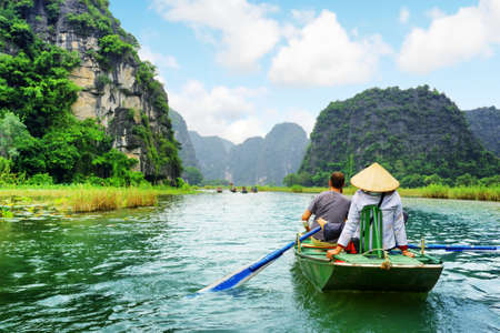 Tourists traveling in boat along the Ngo Dong River at the Tam Coc portion, Ninh Binh Province, Vietnam. Rower using her feet to propel oars. Beautiful landscape formed by karst towers and rice fields