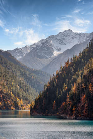 long lake: Amazing view of snow-capped mountains on blue sky background. Snowy peaks, wooded mountains and the Long Lake in Jiuzhaigou nature reserve (Jiuzhai Valley National Park), China. Beautiful landscape. Stock Photo