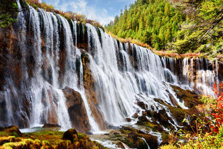 lang: Fantastic view of the Nuo Ri Lang Waterfall (Nuorilang) among woods and mountains in Jiuzhaigou nature reserve (Jiuzhai Valley National Park) of Sichuan province, China. Amazing sunny landscape. Stock Photo