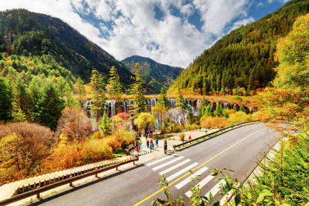 lang: Top view of the Nuo Ri Lang Waterfall (Nuorilang) and road among wooded mountains and colorful fall forest in Jiuzhaigou nature reserve (Jiuzhai Valley National Park), China. Amazing autumn landscape. Stock Photo