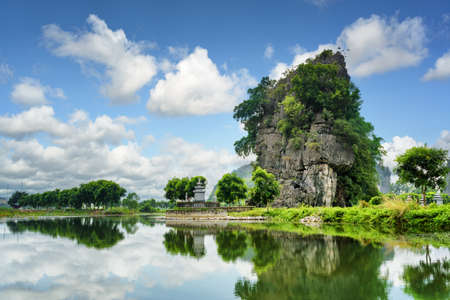 ngo: Scenic natural karst tower reflected in water of the Ngo Dong River at the Tam Coc portion, Ninh Binh Province, Vietnam. Blue sky in background. The Tam Coc is a popular tourist attraction in Asia.