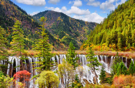lang: Beautiful view of the Nuo Ri Lang Waterfall (Nuorilang) among wooded mountains and colorful fall forest in Jiuzhaigou nature reserve (Jiuzhai Valley National Park), China. Amazing autumn landscape. Stock Photo