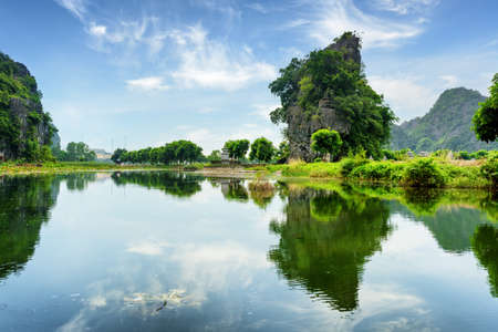 ngo: Beautiful natural karst towers reflected in water of the Ngo Dong River at the Tam Coc portion, Ninh Binh Province, Vietnam. Blue sky in background The Tam Coc is a popular tourist attraction in Asia.