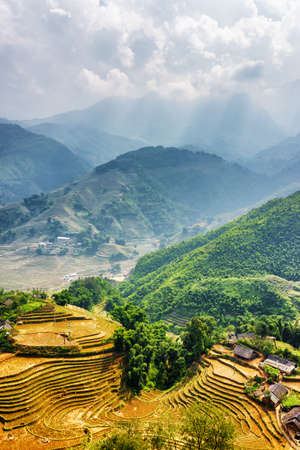 lien: Top view of village houses and rice terraces of Sapa District, Lao Cai Province, Vietnam. Rays of sunlight through clouds in the Hoang Lien Mountains are visible in background.