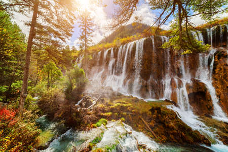 lang: The Nuo Ri Lang Waterfall (Nuorilang) among colorful fall woods in Jiuzhaigou nature reserve (Jiuzhai Valley National Park), China. The sun is shining through foliage of trees. Autumn landscape.