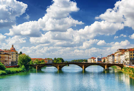 trinita: The Ponte alla Carraia over the Arno River in Florence, Tuscany, Italy. Scenic view from the Ponte Santa Trinita (Holy Trinity Bridge). Florence is a popular tourist destination of Europe. Stock Photo