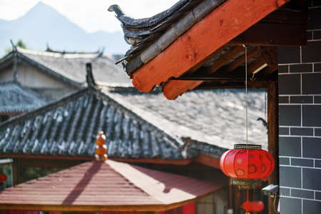old town house: Traditional Chinese tile roof of wooden house decorated with oriental red lantern, the Old Town of Lijiang, China. Others black roofs and mountains are visible in background. Focus on the lantern.