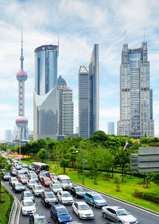 downtown district: SHANGHAI, CHINA - OCTOBER 31, 2015: Modern city traffic on Century Avenue in the Pudong New District (Lujiazui). The Oriental Pearl Tower and other skyscrapers of downtown on blue sky background.
