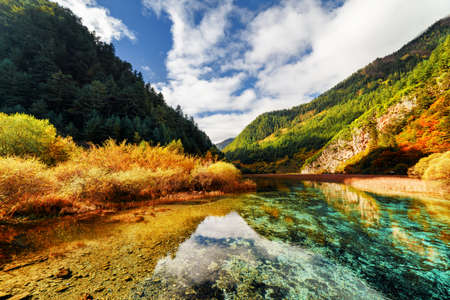 crystal clear: Amazing crystal clear water of river among mountains in autumn, Jiuzhaigou nature reserve (Jiuzhai Valley National Park), China. Evergreen woods in background. Beautiful colorful fall landscape.