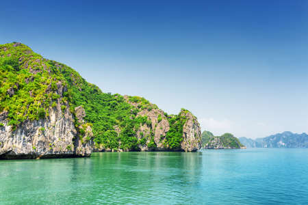 karst: Scenic karst isles on blue sky background in the Ha Long Bay (Descending Dragon Bay) at the Gulf of Tonkin of the South China Sea, Vietnam. The Halong Bay is a popular tourist destination of Asia.