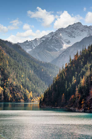 long lake: Beautiful view of snow-capped mountains on blue sky background. Snowy peaks, wooded mountains and the Long Lake in Jiuzhaigou nature reserve (Jiuzhai Valley National Park), China. Amazing landscape.