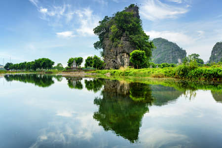 ngo: Scenic natural karst tower reflected in water of the Ngo Dong River at the Tam Coc portion, Ninh Binh Province, Vietnam. The Tam Coc is a popular tourist attraction in Asia.