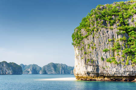 destination scenic: Scenic karst tower-isle with white wild beach in the Halong Bay (Descending Dragon) at the Gulf of Tonkin of the South China Sea, Vietnam. The Ha Long Bay is a popular tourist destination of Asia. Stock Photo
