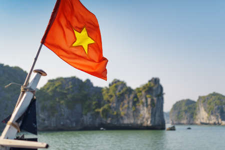 The flag of Vietnam (red flag with a gold star) fluttering on ship in the Halong Bay at the Gulf of Tonkin of the South China Sea, Vietnam. Karst towers-isles are visible in background.