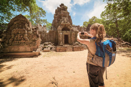 Young female tourist with blue backpack and smartphone taking picture of the gopura and the bas-relief near the entrance to ancient Preah Khan temple in Angkor. Siem Reap, Cambodia. Toned image.