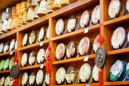 pu: LIJIANG, YUNNAN PROVINCE, CHINA - OCTOBER 23, 2015: Traditional Chinese tea on wooden shelves at tea shop, the Old Town of Lijiang. Disks of post-fermented tea Yunnan Puer. Shallow depth of field.