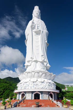 bodhisattva: View of the Lady Buddha (the Bodhisattva of Mercy) at the Linh Ung Pagoda, Danang (Da Nang), Vietnam. Majestic white Buddha statue on blue sky background. Stock Photo