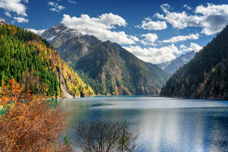 long lake: Scenic view of the Long Lake among mountains and colorful fall woods in Jiuzhaigou nature reserve (Jiuzhai Valley National Park), China. Beautiful snowy peaks and blue sky are visible in background. Stock Photo