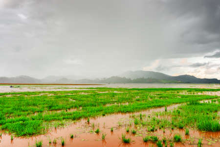 tay: Scenic view of the Lak Lake on a rainy day. Amazing summer landscape at the Tay Nguyen (the Central Highlands) in Dak Lak Province (Daklak) of Vietnam. Mountains in rain are visible in background. Stock Photo