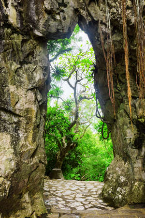 Scenic view of gate in rocks and brick walkway leading into enigmatic tropical garden. Green trees of woods are visible across gate at the Marble Mountains (Ngu Hanh Son), Vietnam. Forest in summer.