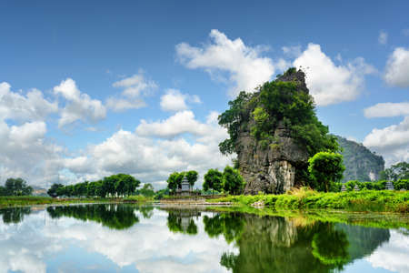 ngo: Beautiful natural karst tower reflected in water of the Ngo Dong River at the Tam Coc portion, Ninh Binh Province, Vietnam. The Tam Coc is a popular tourist attraction in Asia.