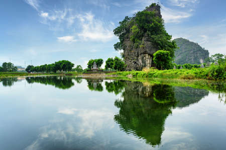 ngo: Amazing natural karst tower reflected in water of the Ngo Dong River at the Tam Coc portion, Ninh Binh Province, Vietnam. The Tam Coc is a popular tourist attraction in Asia. Stock Photo
