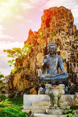 nang: Majestic black Buddha statue near rock. The Linh Ung Pagoda in Danang (Da Nang), Quang Nam Province, Vietnam. Danang is a popular tourist destination of Asia. Toned image.