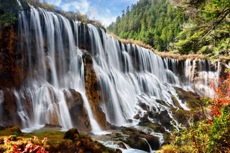 lang: Amazing view of the Nuo Ri Lang Waterfall (Nuorilang) among woods and mountains in Jiuzhaigou nature reserve (Jiuzhai Valley National Park) of Sichuan province, China. Fantastic sunny landscape. Stock Photo