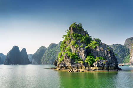 Scenic view of the Halong Bay (Descending Dragon Bay) at the Gulf of Tonkin of the South China Sea, Vietnam. Landscape formed by karst towers-isles in various sizes and shapes. Blue sky in background
