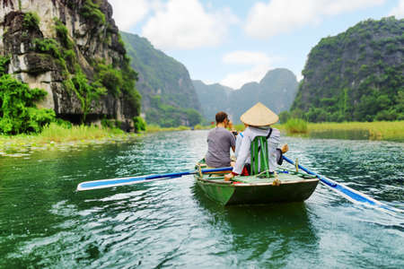 propel: Tourists traveling in small boat along the Ngo Dong River at the Tam Coc portion, Ninh Binh Province, Vietnam. Rower using her feet to propel oars. Landscape formed by karst towers and rice fields.