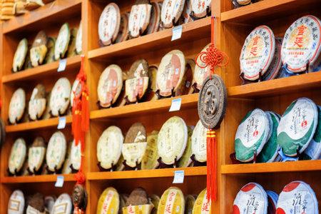 pu: LIJIANG, YUNNAN PROVINCE, CHINA - OCTOBER 23, 2015: Traditional Chinese tea on wooden shelves at tea shop, the Old Town of Lijiang. Disks of post-fermented tea Yunnan Puer. Editorial
