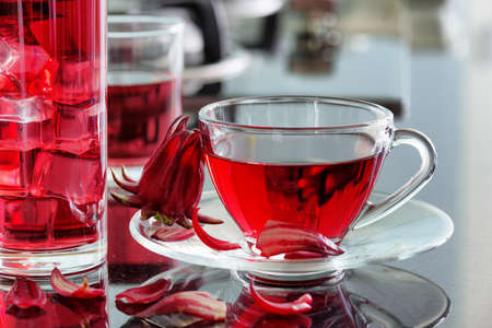 sepals: Cup of hibiscus tea (rosella, karkade, red sorrel, Agua de flor de Jamaica) on kitchen table. The same drink with ice cubes in glass. Drink made from magenta calyces (sepals) of roselle flowers.
