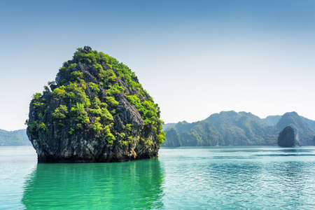 destination scenic: Scenic karst isle on blue sky background in the Ha Long Bay (Descending Dragon Bay) at the Gulf of Tonkin of the South China Sea, Vietnam. The Halong Bay is a popular tourist destination of Asia.