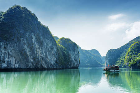 halong: Tourist boat in the Halong Bay (Descending Dragon Bay) at the Gulf of Tonkin of the South China Sea, Vietnam. Landscape formed by karst isles. The Ha Long Bay is a popular tourist destination of Asia