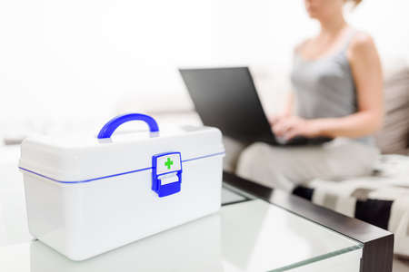 first aid box: White plastic box with first aid kit on table. Woman with laptop choosing pills in internet pharmacy and getting online medical consultation with doctor at home.