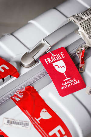 handle with care: Nha Trang, Vietnam - August 16, 2016: Closeup view of bright red luggage tag (Fragile, Handle with care) attached to white plastic suitcase at airport. Editorial