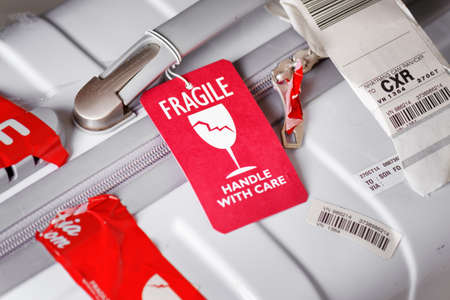 handle with care: Nha Trang, Vietnam - August 16, 2016: Closeup view of bright red luggage tag (Fragile, Handle with care) attached to white plastic suitcase at airport of Cam Ranh.