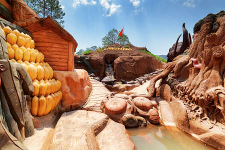dalat: Dalat, Vietnam - March 31, 2016: Amazing canyon with clay houses and sculptures of animal and vegetables at the Dalat Star. Man-made waterfall in artificial mountain is visible on blue sky background.