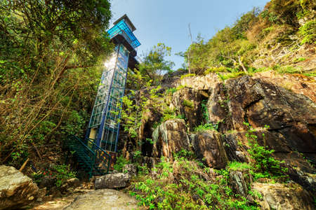 dalat: Bottom view of beautiful glass tower among green woods and rocks on blue sky background. Amazing outdoor elevator in forest of Vietnam. The sun reflected in glass wall of tower.