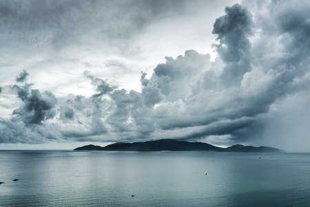 storm clouds: Scenic seascape with dramatic stormy sky. Rain is visible at right. Wonderful view of Nha Trang Bay, the South China Sea, Vietnam.