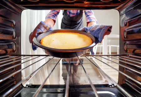 Housewife using dishcloth for taking cheesecake out of oven in kitchen. View from inside of the oven. Woman wearing colorful checkered shirt and black apron.
