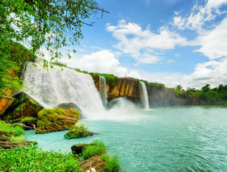 tay: The Dray Nur Waterfall on the Serepok River among green woods at the Tay Nguyen (the Central Highlands) in Dak Lak Province (Daklak) of Vietnam. Summer landscape with azure pond and blue sky. Stock Photo