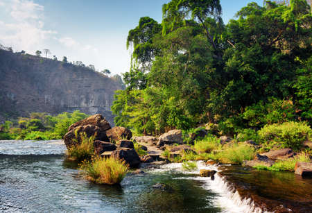 Scenic river with crystal clear water among green woods and rocks in summer. Beautiful forest landscape in Vietnam. The Da Nhim River (Krong Pha or Song Pha) is a popular tourist destination of Asia.
