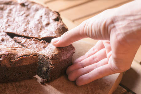 porcion de torta: Closeup view of hand taking piece of freshly baked chocolate brownie cake with walnuts. Homemade delicious sweet dessert on wooden board, family meal.