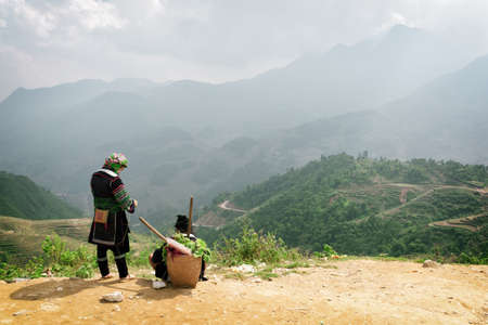 green clothes: Sapa (Sa Pa), Vietnam - October 19, 2015: Hmong women in national clothes on mountain top at highlands of Sapa District (Sa Pa), Lao Cai Province. Scenic green rice terraces in background.