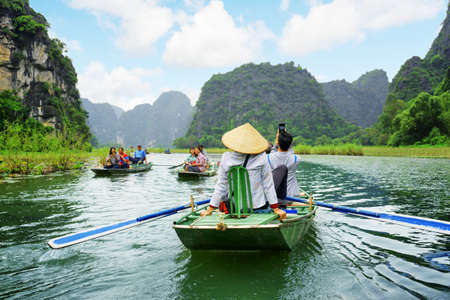 NINH BINH PROVINCE, VIETNAM - OCTOBER 14, 2015: Tourists traveling in boats along the Ngo Dong River at the Tam Coc portion. Rowers using their feet to propel oars. Landscape formed by karst towers. Stockfoto